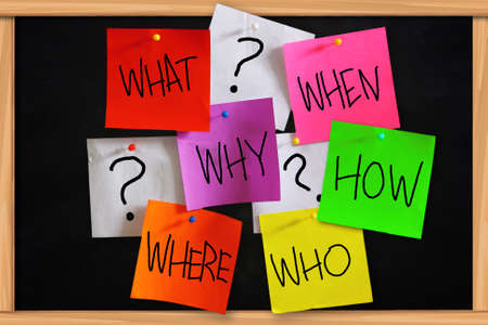 Concept of basic questions written on sticky colored paper