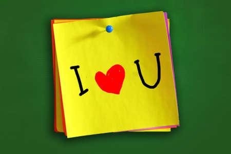 te quiero: La palabra Te amo con el símbolo del corazón escrito en papel de color pegajoso Foto de archivo