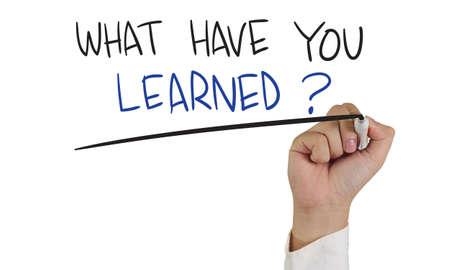 Imagen del concepto motivación de una participación marcador de la mano y escribir lo que has aprendido aislado en blanco Foto de archivo