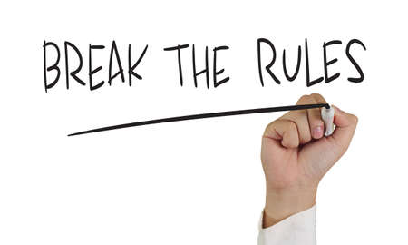 Motivational concept image of a hand holding marker and write Break the Rules isolated on white photo