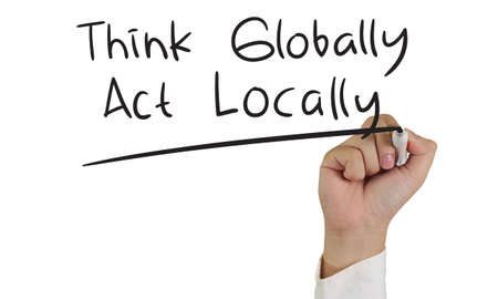 globally: Motivational concept image of a hand holding marker and write Think Globally Act Locally isolated on white