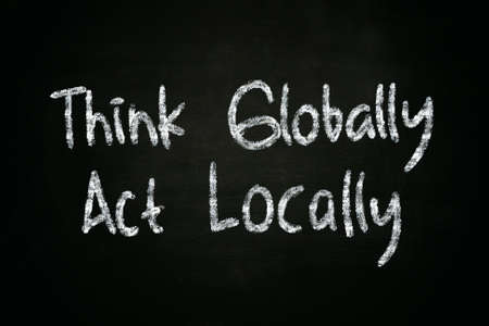 globally: The words Think Globally Act Locally written with chalk on blackboard