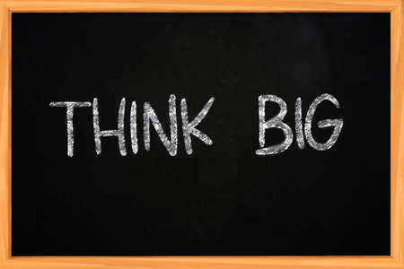 The words Think Big written with chalk on blackboard photo