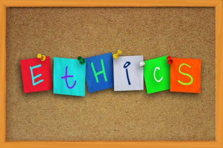 conduct: The word Ethics written on sticky colored paper over cork board Stock Photo