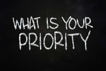 crucial: The words What is your priority written with chalk on blackboard