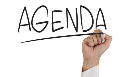 Image of a hand holding marker and write Agenda word isolated on white