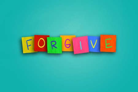 perdonar: La palabra Forgive escrito en papel de color pegajoso