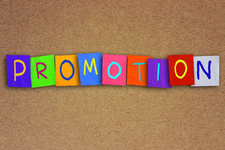 colored paper: The word promotion written on sticky colored paper over cork board Stock Photo