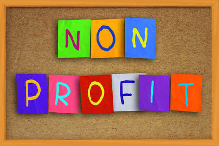 colored paper: The words Non Profit written on sticky colored paper over cork board Stock Photo