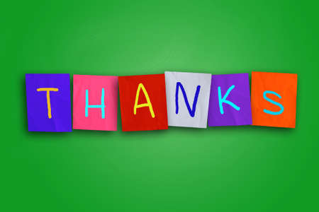 colored paper: The word thanks you written on sticky colored paper over cork board