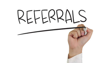 referral: Image of a hand holding marker and write referrals word isolated on white Stock Photo