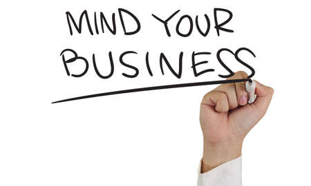 business mind: Image of a hand holding marker and write mind your business words isolated on white Stock Photo