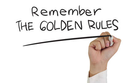 rule: Business concept image of a hand holding marker and write Remember the Golden Rules words isolated on white