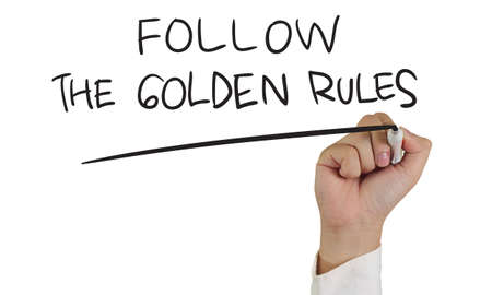 golden rule: Business concept image of a hand holding marker and write Follow the Golden Rules words isolated on white