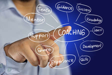 coaches: Business concept image of a businessman pointing Coaching icon on virtual screen over blue background