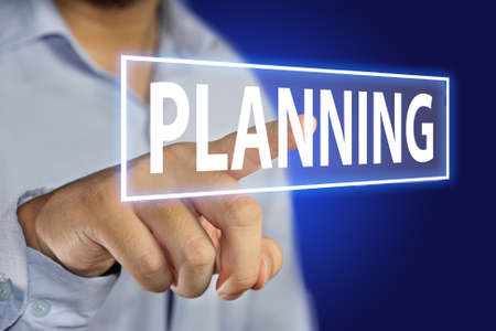 motivating: Business concept image of a businessman pointing Planning icon on virtual screen over blue background