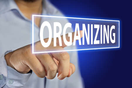Business concept image of a businessman pointing Organizing icon on virtual screen over blue background