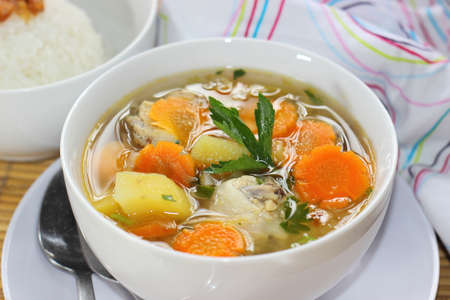 A bowl of Chicken Soup served with slices of potato and carrots