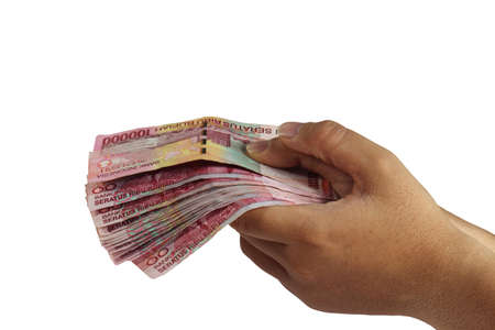 Image of hand holding 100000 Rupiah isolated on white Stock Photo