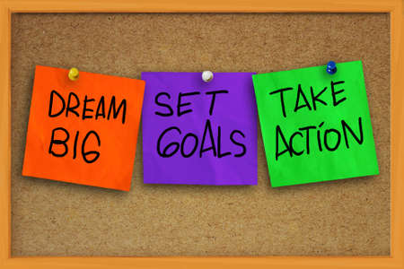 The words Dream Big, Set Goals, Take Action written on sticky colored paper over cork board
