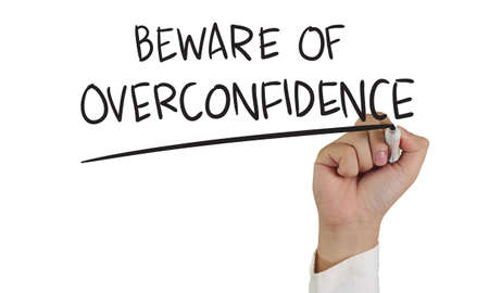jerk: Business concept image of a hand holding marker and write Beware of Overconfidence isolated on white Stock Photo