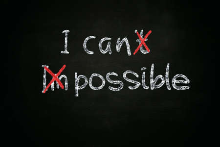 unable: Business motivational concept the words I Can and Possible written with chalk on blackboard