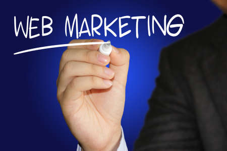 Business concept image of a businessman holding marker and write Web Marketing on blue background Stock Photo