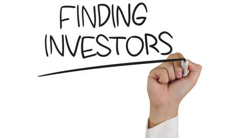 investors: Business concept image of a hand holding marker and write Finding Investors on white Stock Photo