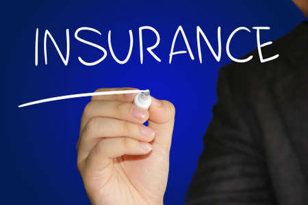 insurer: Business concept image of a hand holding marker and write Insurance over blue background