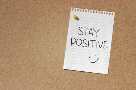positive feelings: Motivational Concept Image of message note paper pinned on cork board with Stay Positive words written on it Stock Photo