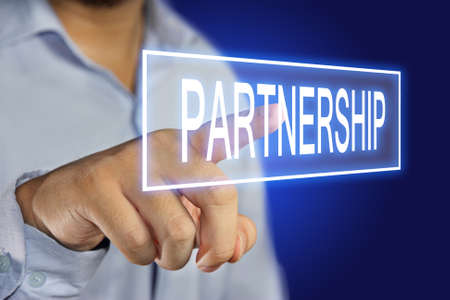 synergism: Business concept image of a businessman clicking Partnership button on virtual screen over blue background Stock Photo
