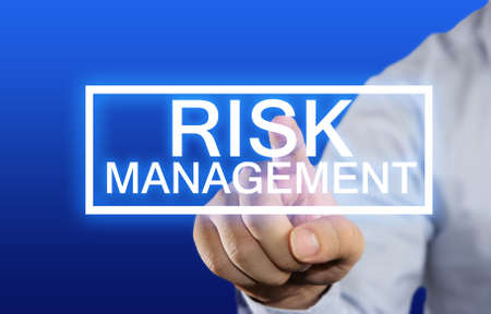 erm: Business concept image of a businessman clicking Risk Management button on virtual screen over blue background