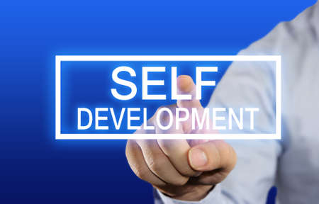 self development: Business concept image of a businessman clicking Self Development button on virtual screen over blue background Stock Photo