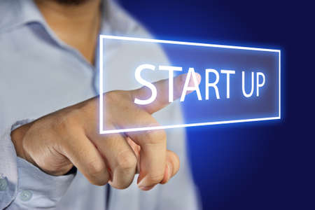 start button: Business concept image of a businessman clicking Start Up button on virtual screen over blue background Stock Photo