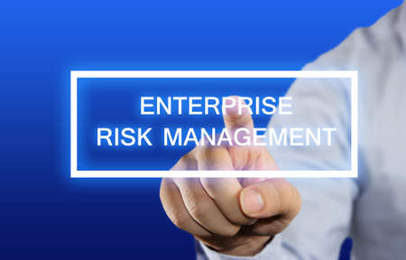 enterprise: Business concept image of a businessman clicking Enterprise Risk Management button on virtual screen over blue background