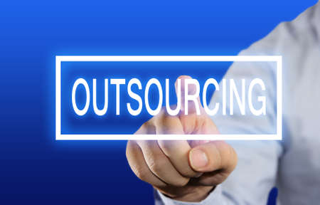 offshoring: Business concept image of a businessman clicking Outsourcing button on virtual screen over blue background