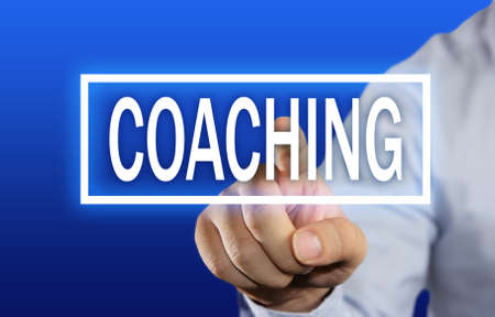 Business concept image of a businessman clicking Coaching button on virtual screen over blue background