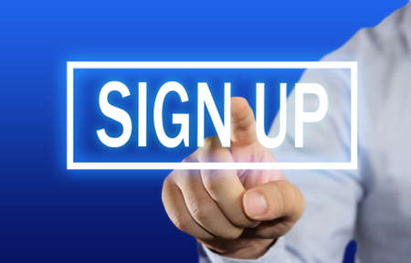 sign up button: Business concept image of a businessman clicking Sign Up button on virtual screen over blue background