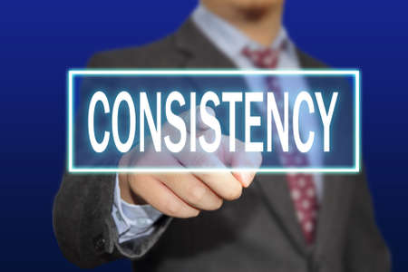 consistency: Business concept image of a businessman clicking Consistency button on virtual screen over blue background Stock Photo
