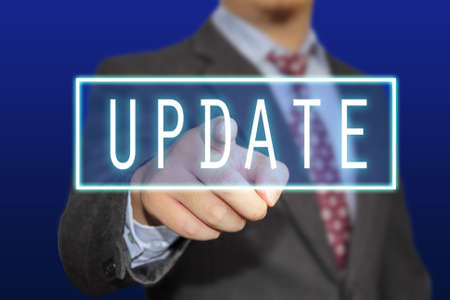 refresh button: Business concept image of a businessman clicking Update button on virtual screen over blue background