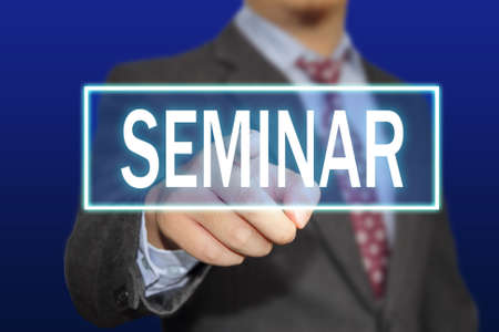 learning concept: Business concept image of a businessman clicking Seminar button on virtual screen over blue background