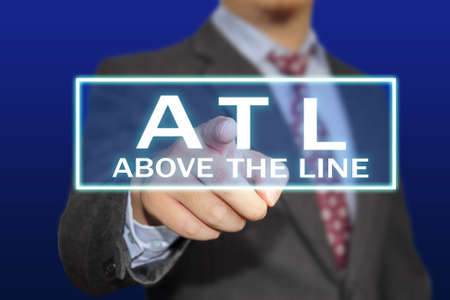 Advertising concept image of a businessman clicking ATL or Above The Line button on virtual screen over blue background