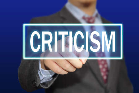 criticism: Business concept image of a businessman clicking Criticism button on virtual screen over blue background