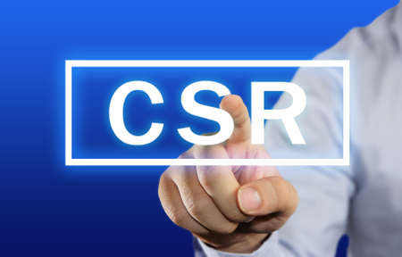 csr: Business concept image of a businessman clicking CSR or Corporate Social Responsibility button on virtual screen over blue background Archivio Fotografico