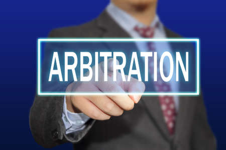 arbitration: Business concept image of a businessman clicking Arbitration button on virtual screen over blue background