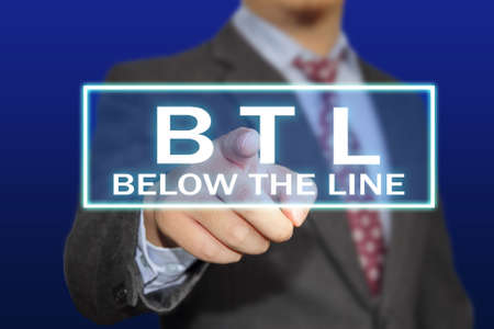 Advertising concept image of a businessman clicking BTL or Below The Line button on virtual screen over blue background