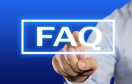 frequently asked question: Business concept image of a businessman clicking FAQ or Frequently Asked Question button on virtual screen over blue background