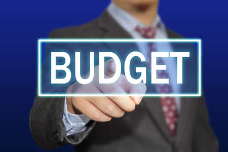 budget crisis: Business concept image of a businessman clicking Budget button on virtual screen over blue background