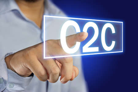 Business concept image of a businessman clicking C2C button on virtual screen over blue background photo
