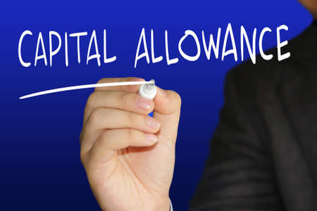 Business concept image of a businessman holding marker and write Capital Allowance over blue background photo